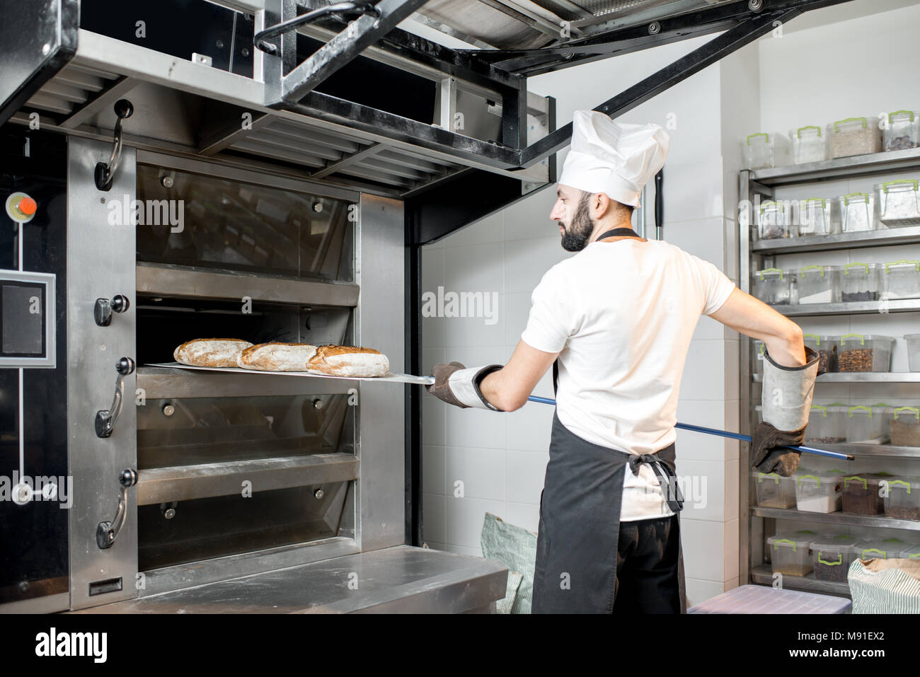Baker taking off the breads from the oven - Stock Image