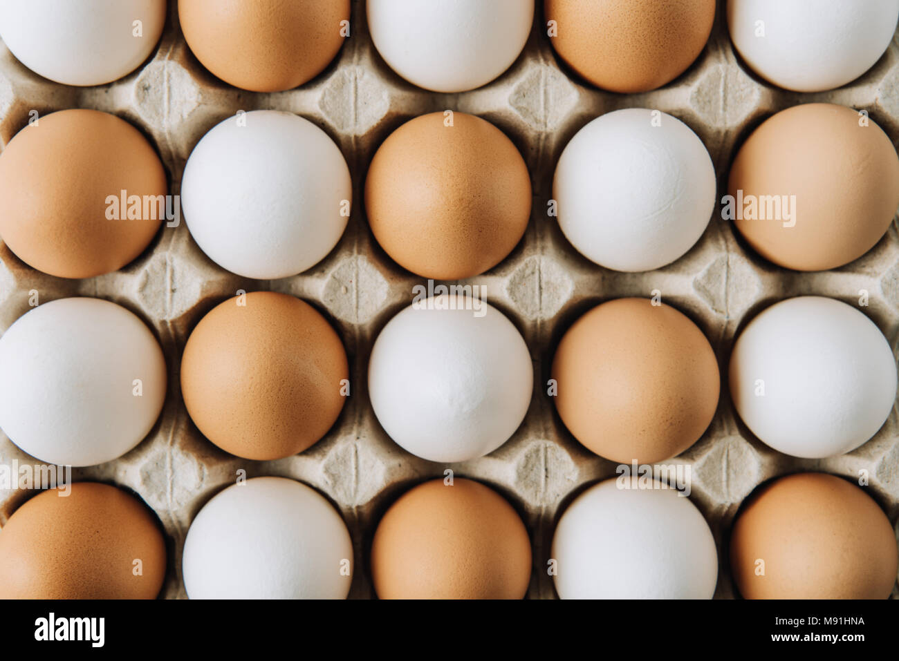 white and brown eggs laying in egg