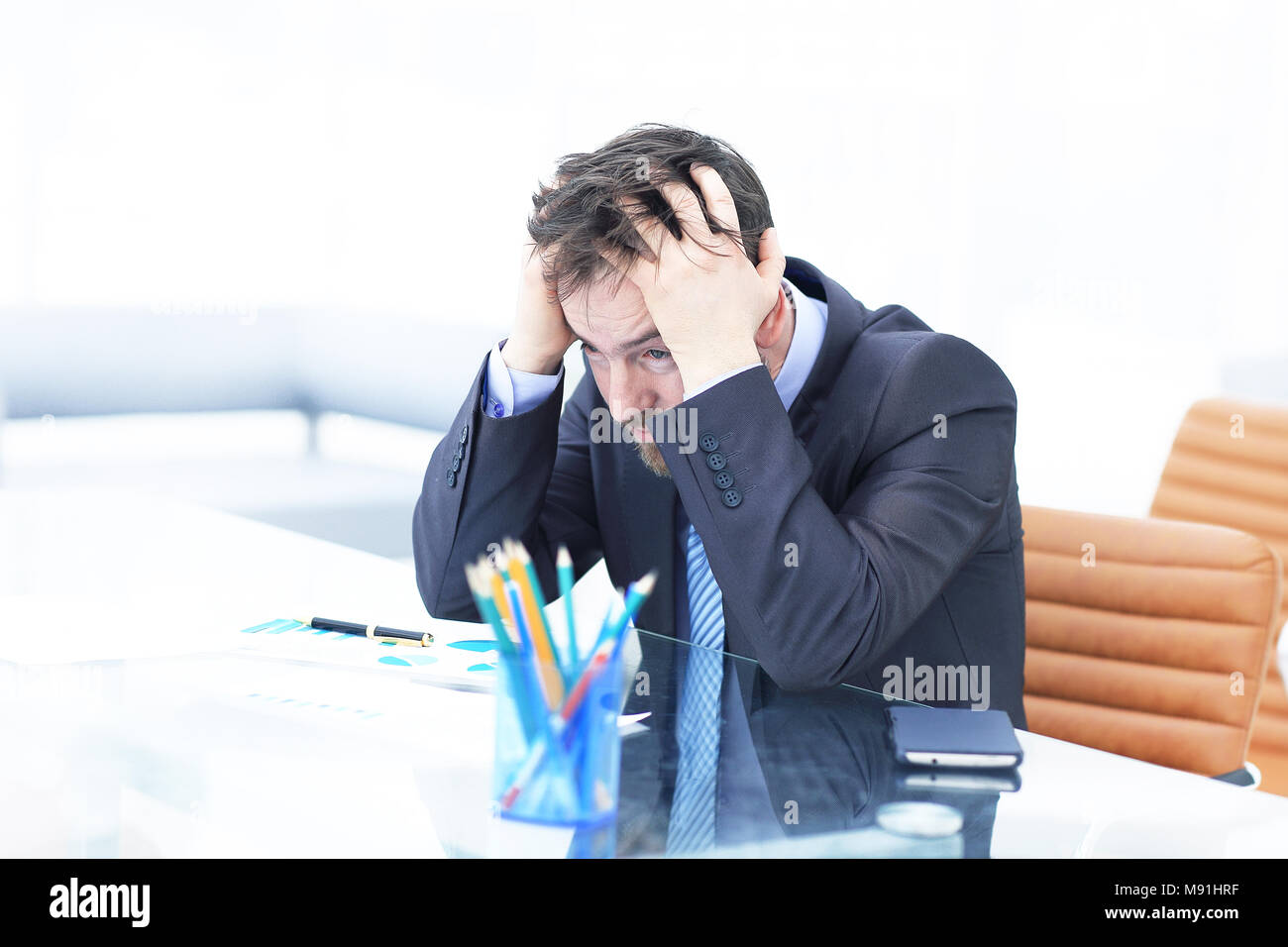 Tired business man at workplace in office holding his head on hands. Sleepy worker early in the morning after late night work. Overworking, making mistake, stress, termination or depression concept - Stock Image