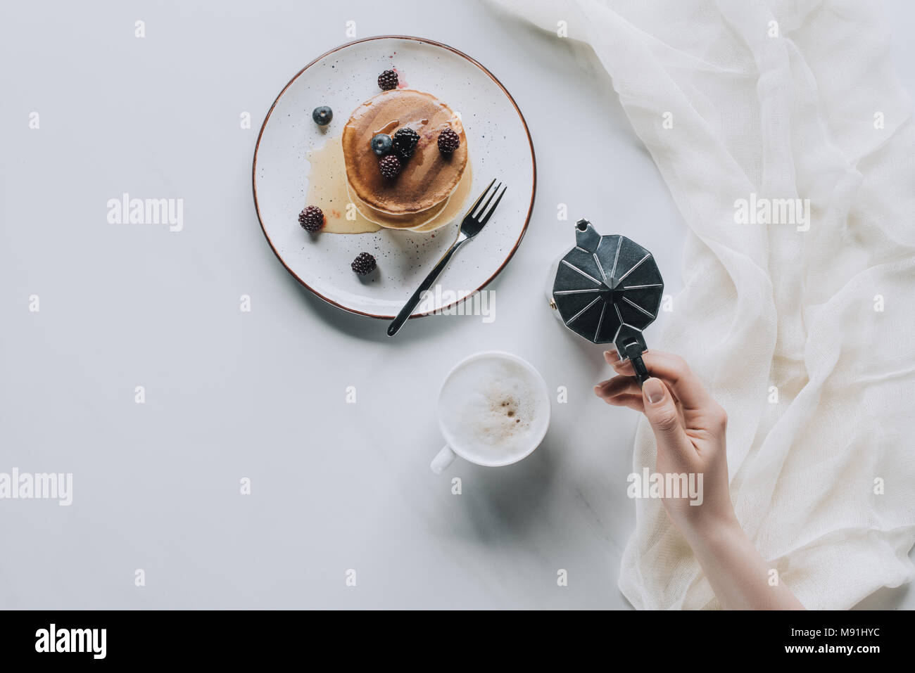 top view of person holding coffee maker while eating pancakes with berries for breakfast - Stock Image