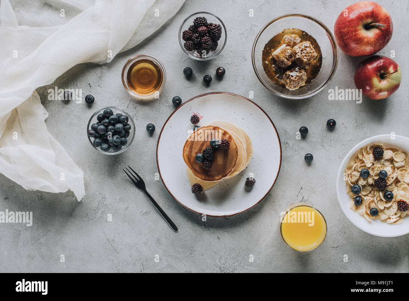 top view of healthy breakfast with homemade pancakes, fresh fruits and honey on grey - Stock Image