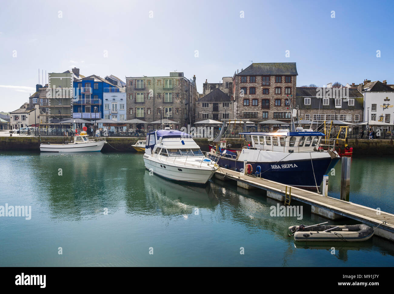 Boats moored in Sutton Harbour, with Quay Road beyond, Plymouth, UK. - Stock Image