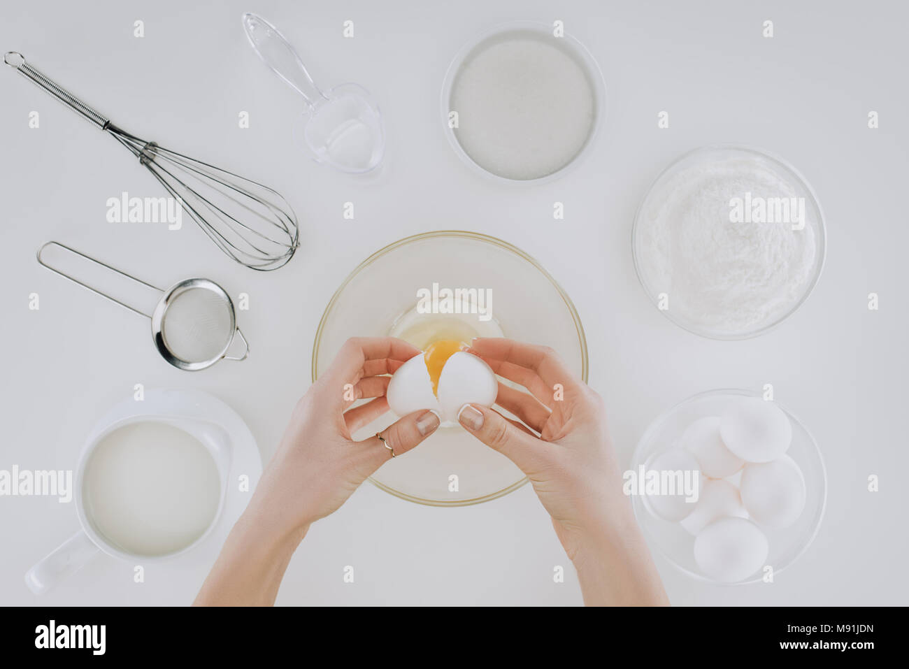 cropped shot of person holding egg while cooking pancakes isolated on grey - Stock Image