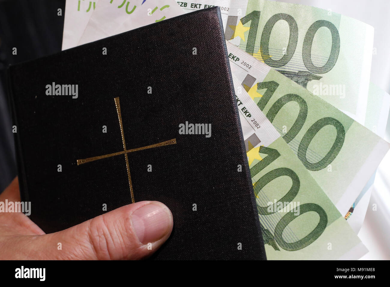 Money and religion. Holy bible and euros. - Stock Image
