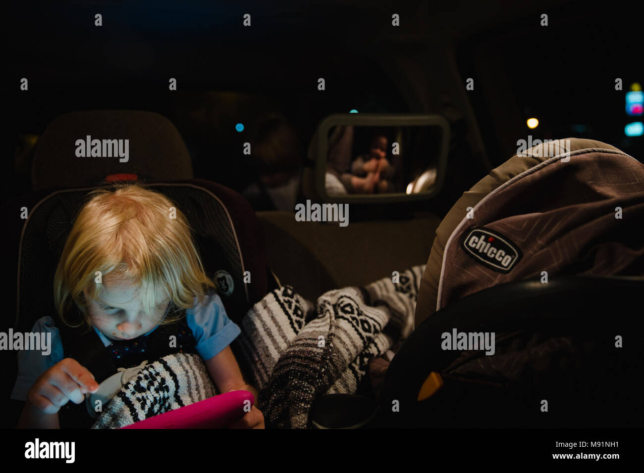 girl plays on ipad tablet in backseat while baby sleeps in carseat night time - Stock Image
