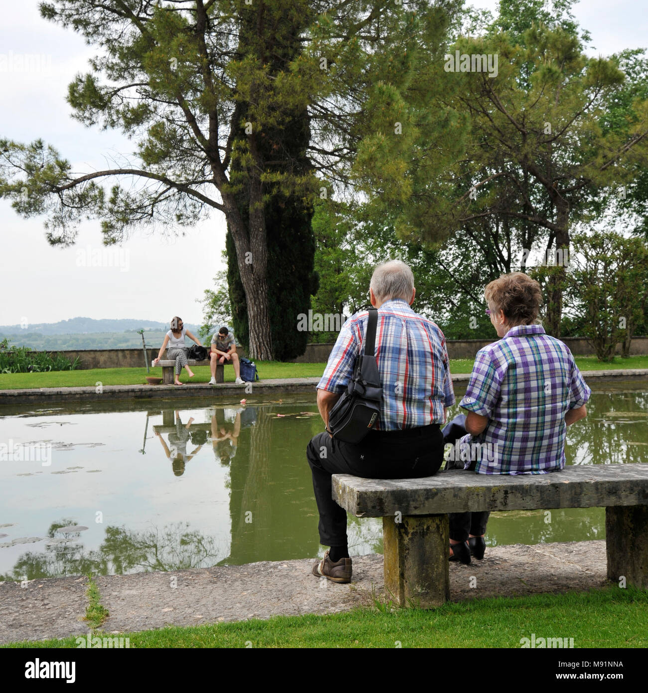 Romantic old couple sitting on park bench by lake. In front of them there is a couple of young lovers who fight. - Stock Image
