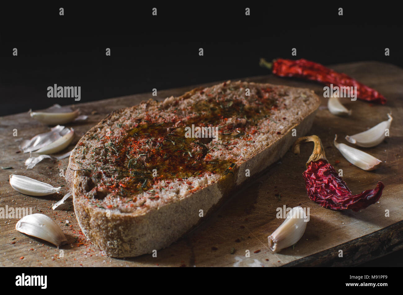 Slice of bread with olive oil pepper, savory, salt and garlic on the wooden board - Stock Image