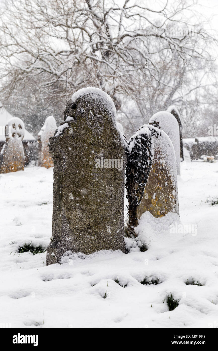 Snow falls on Graves in cemetery, burial ground, churchyard, memorial park, necropolis, burial place, burying place, garden of remembrance - Stock Image