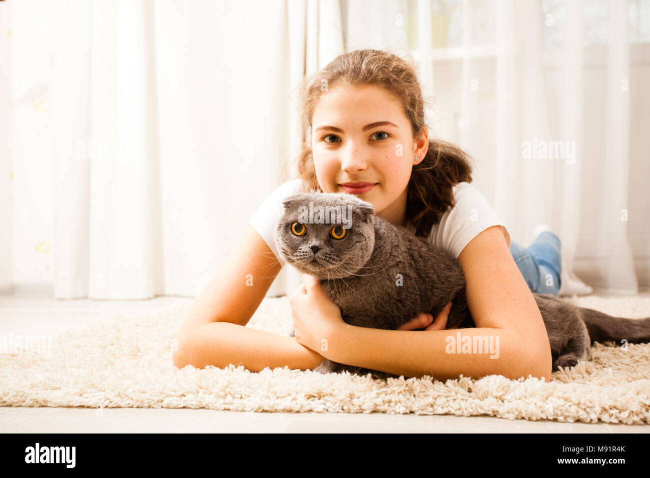 the girl is huging her cat - Stock Image