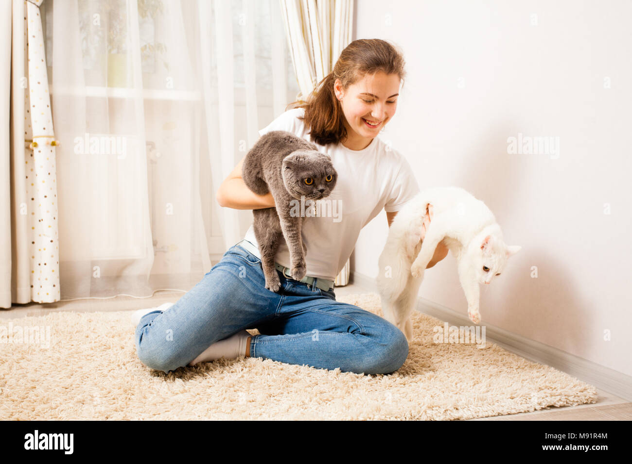 The girlis is holding cats - Stock Image