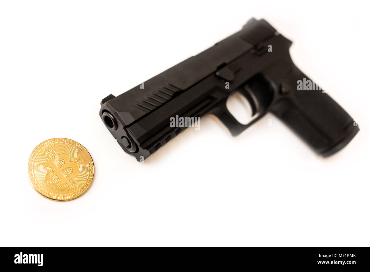 Bitcoin cryptocurrency under a pointing gun theft white background - Stock Image