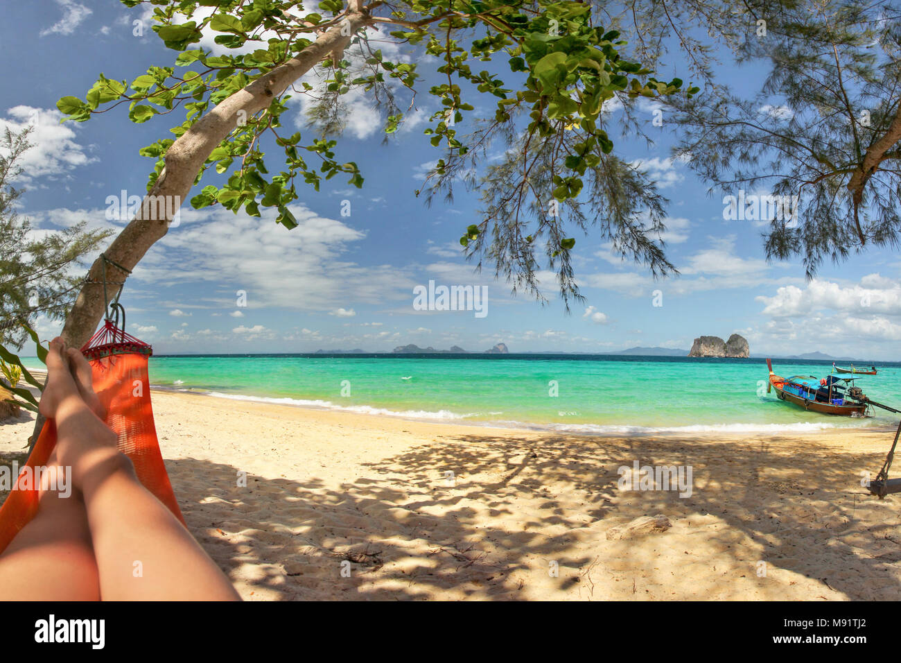 Legs of man laying in red hammock in tree shade with fine sand beach below and view to postcard perfect aquamarine color sea ad little islands in dist - Stock Image