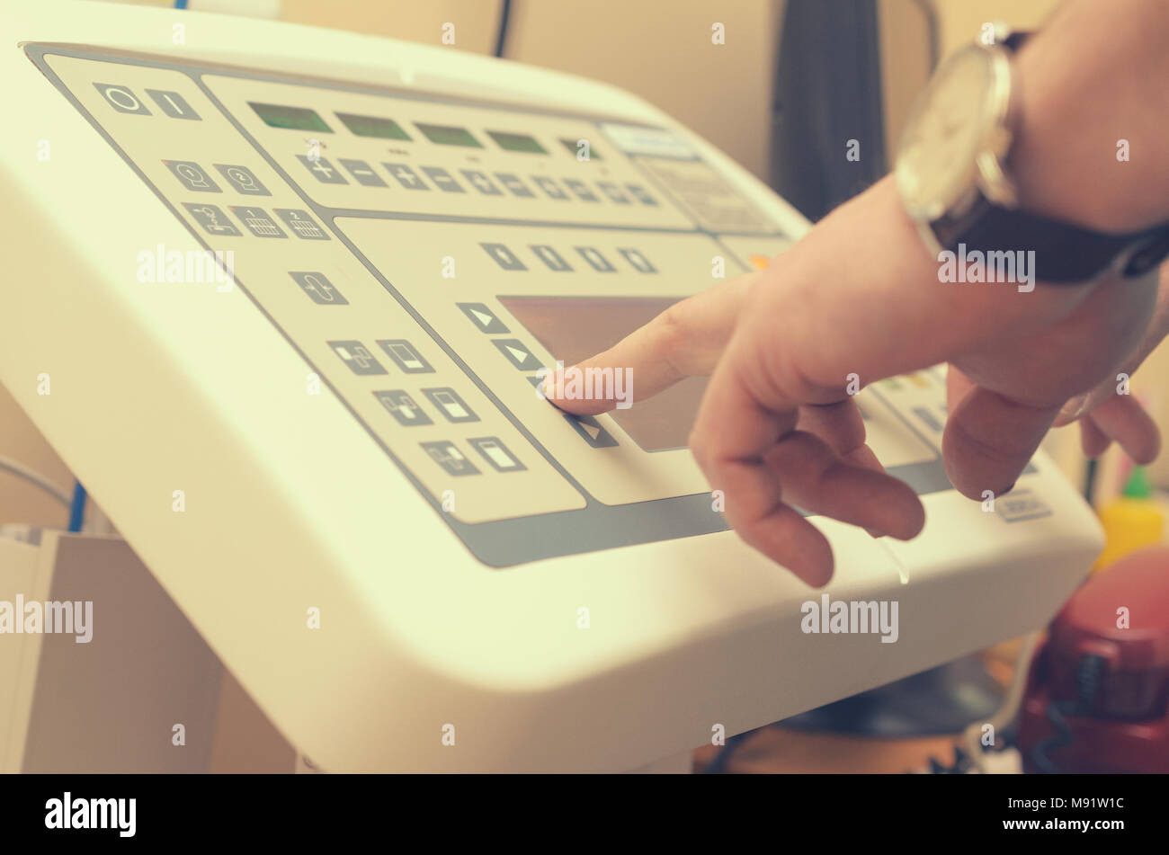 The radiologist presses the button of the control panel to produce an X-ray image. Stock Photo