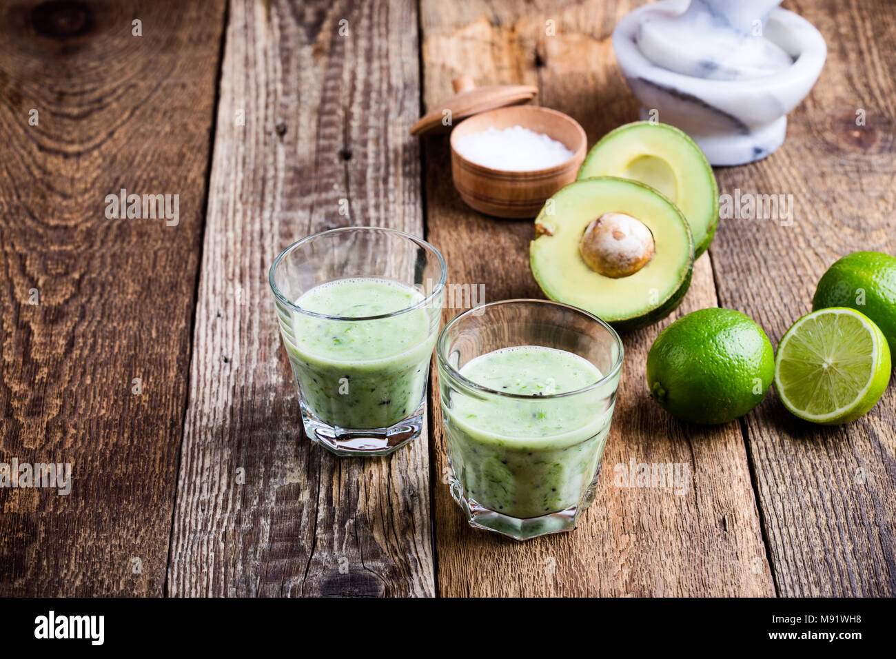 Guacamole dip style green vegetables smoothie in glasses with ingredients avocado and lime on rustic wooden table, savory healthy dairy drink with org - Stock Image