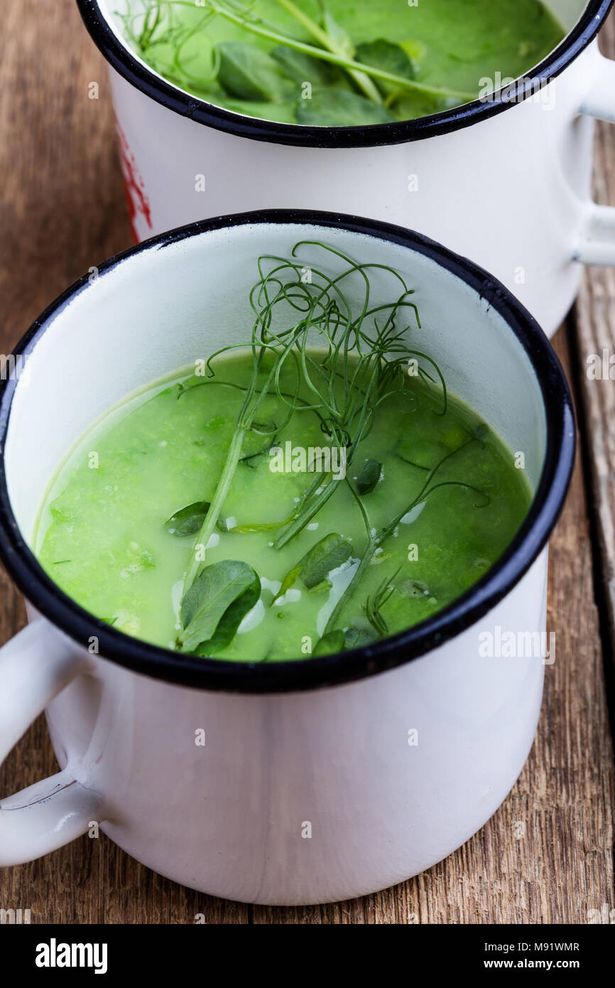 Cream soup with green pea, fresh herbs and sprouts with micro greens on top in rural mugs, healthy vegetarian meal - Stock Image