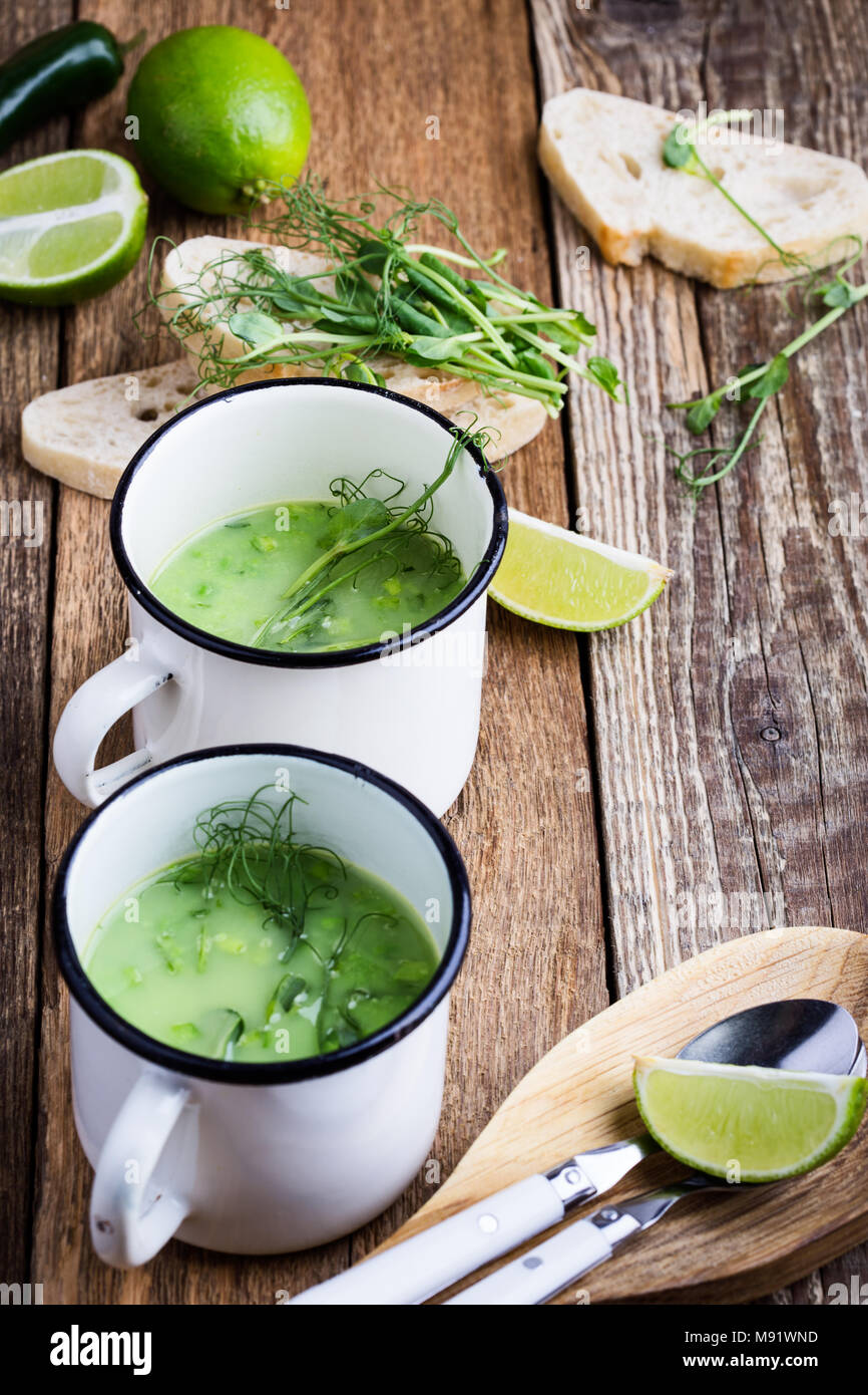 Cream soup with green pea, fresh herbs and sprouts with micro greens on top in rural mugs, healthy vegetarian meal Stock Photo
