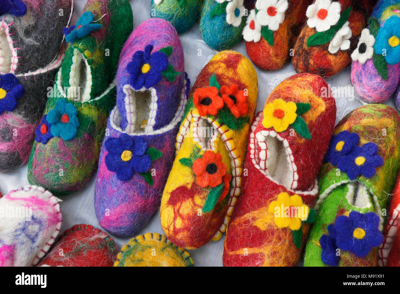 Colorful floral-design wool slippers for sale by a street vendor in Old Town, Tbilisi, Georgia - Stock Image