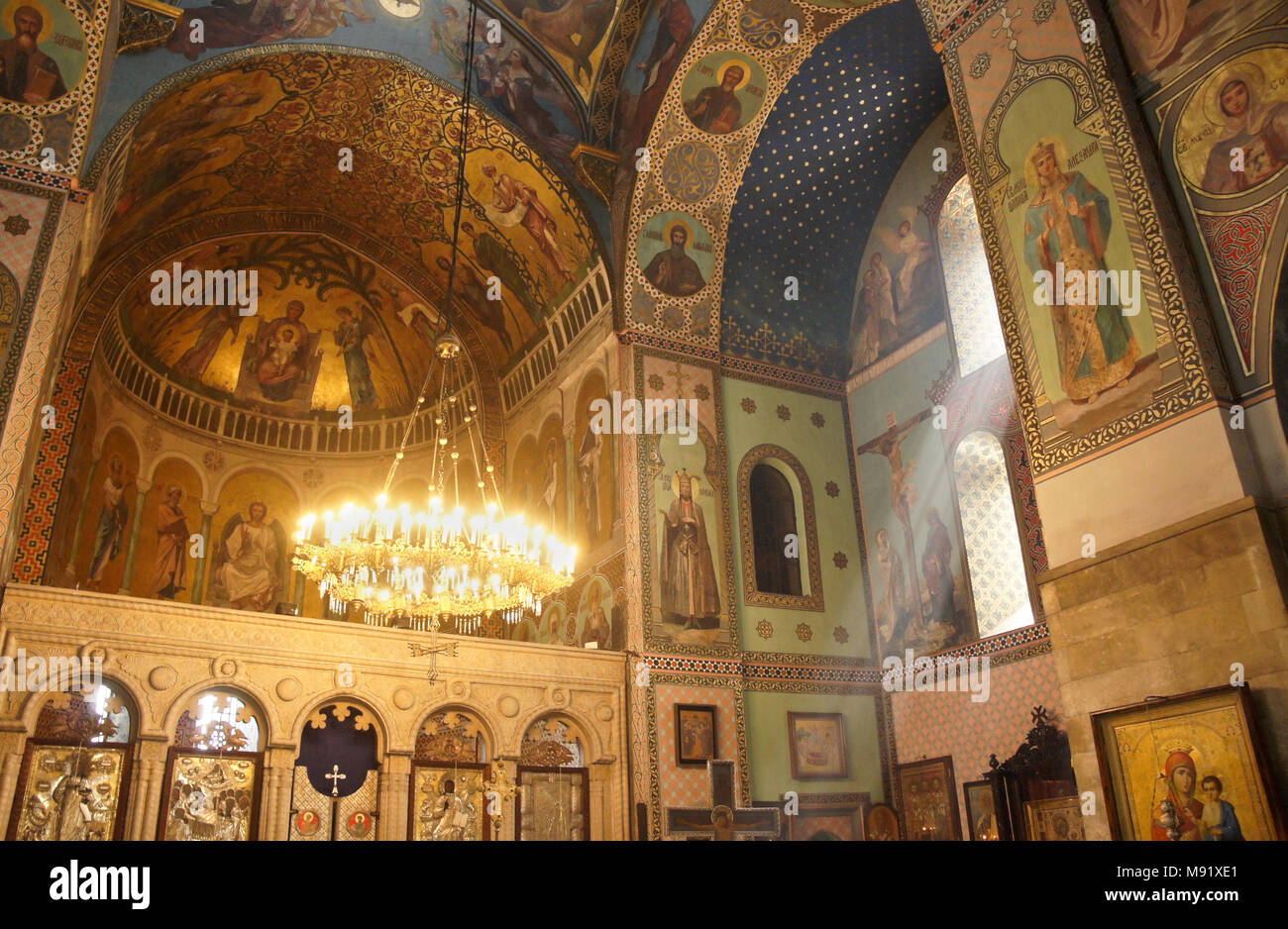 Murals and frescos decorate the Interior of Sioni Cathedral (Georgian Orthodox) as rays of sunlight enter through a side window, Tbilisi, Georgia Stock Photo