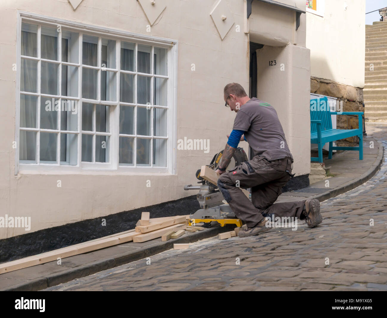 Carpenter refurbishing a cottage using a woodworking electric power saw to cut timber to size on the pavement outside - Stock Image