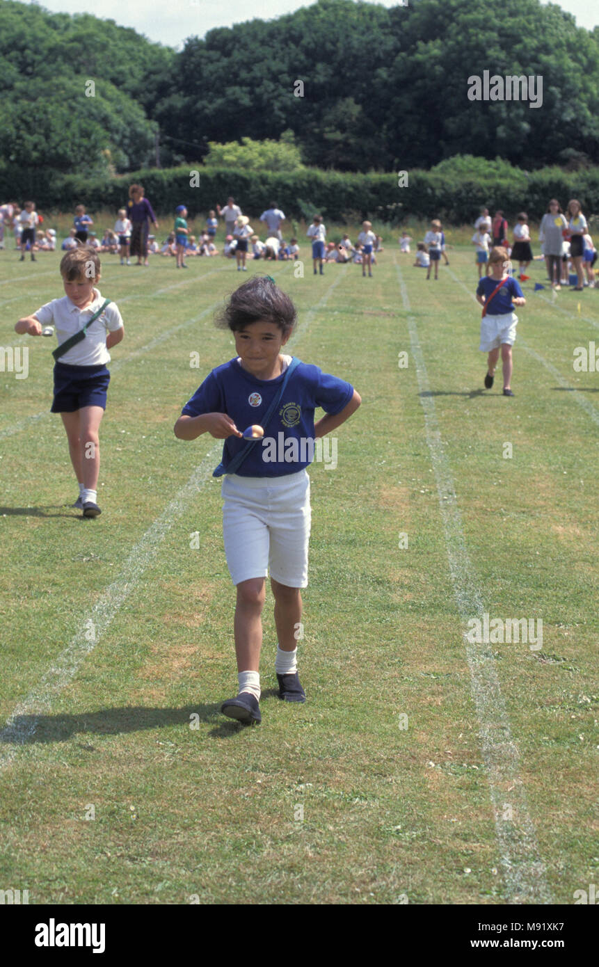 primary school chldren competing in egg and spoon race during sports day, England, UK - Stock Image