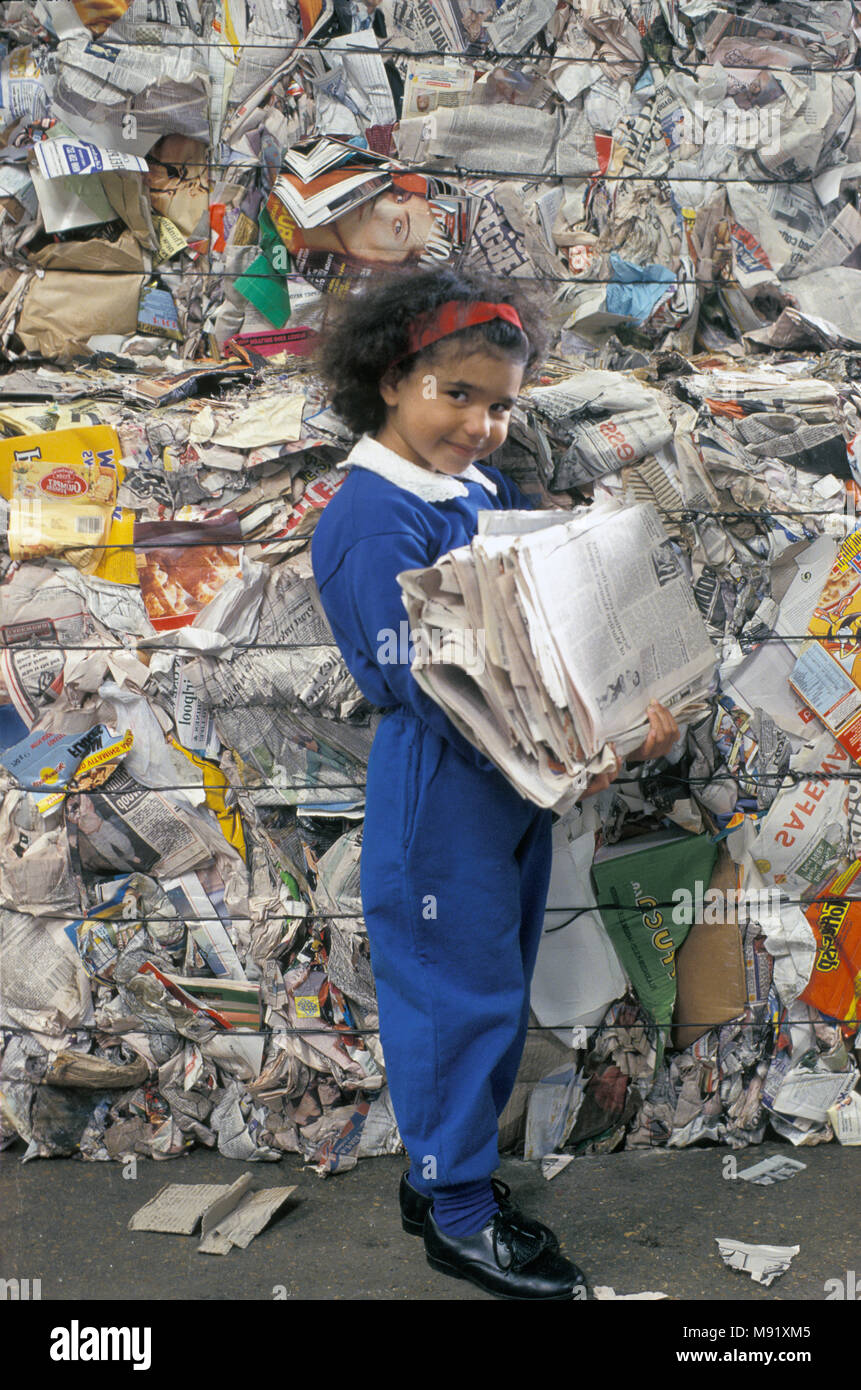 multicultural little girl in paper standing in paper recycling plant holding bunch of newspapers - Stock Image