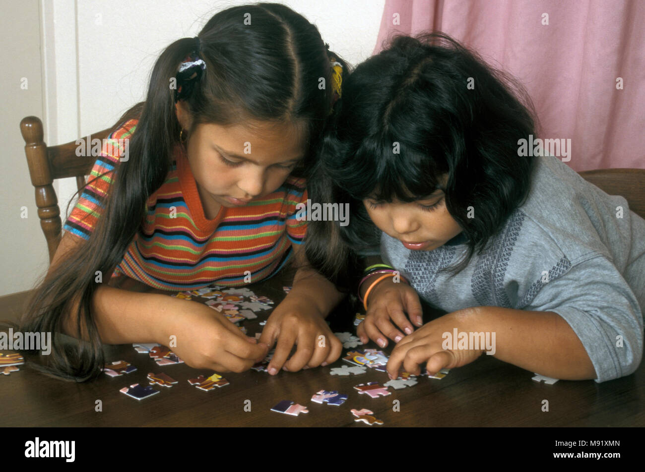 Two Asian sisters doing jigsaw puzzle - Stock Image