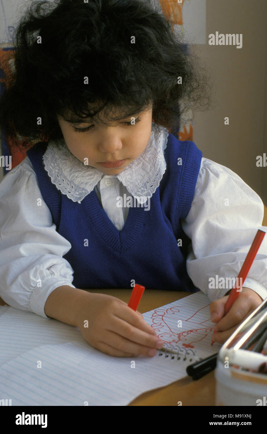 multicultural little girl in school drawing with left hand - Stock Image