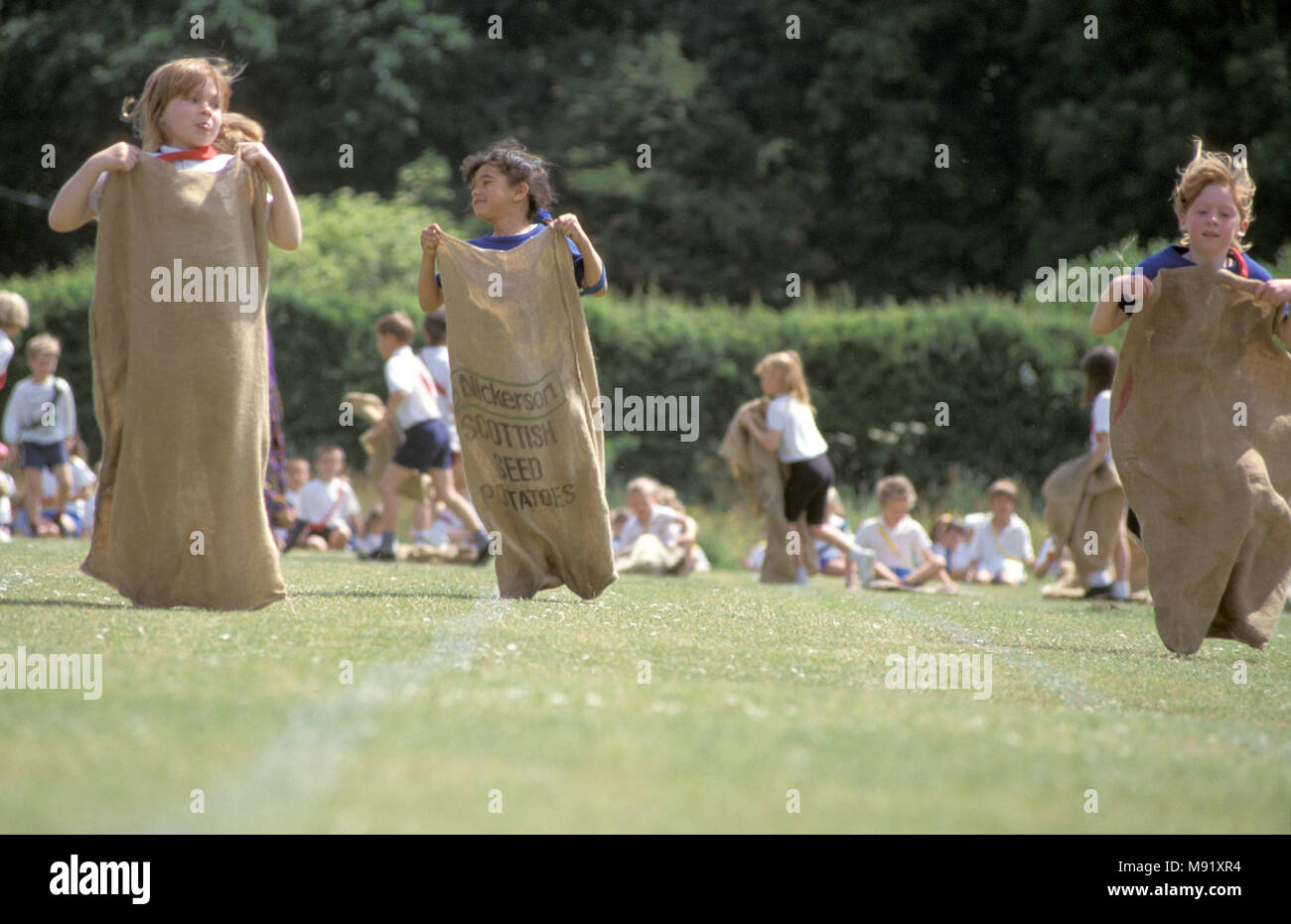 Girls competing in sack race during primary school sports day, England, UK - Stock Image
