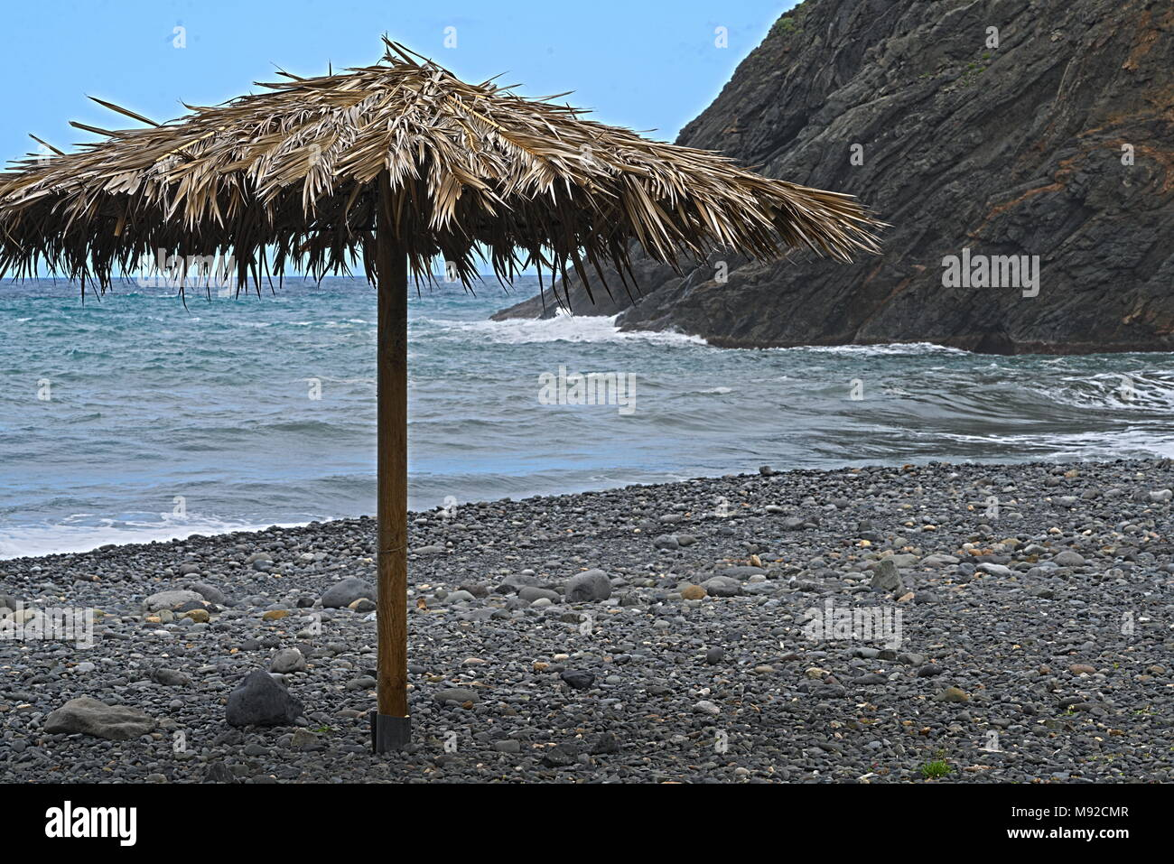 palm  branch parasol at a lonely stone beach, the ocean and a blue sky in the background - Stock Image