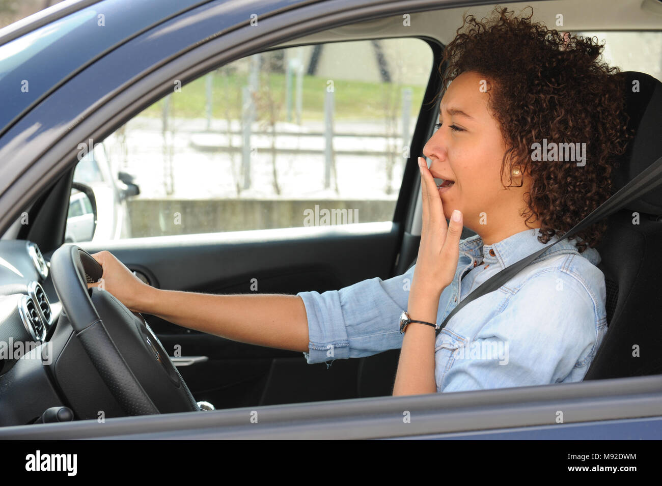 Portrait sleepy tired fatigued exhausted young attractive woman driving her car - Stock Image