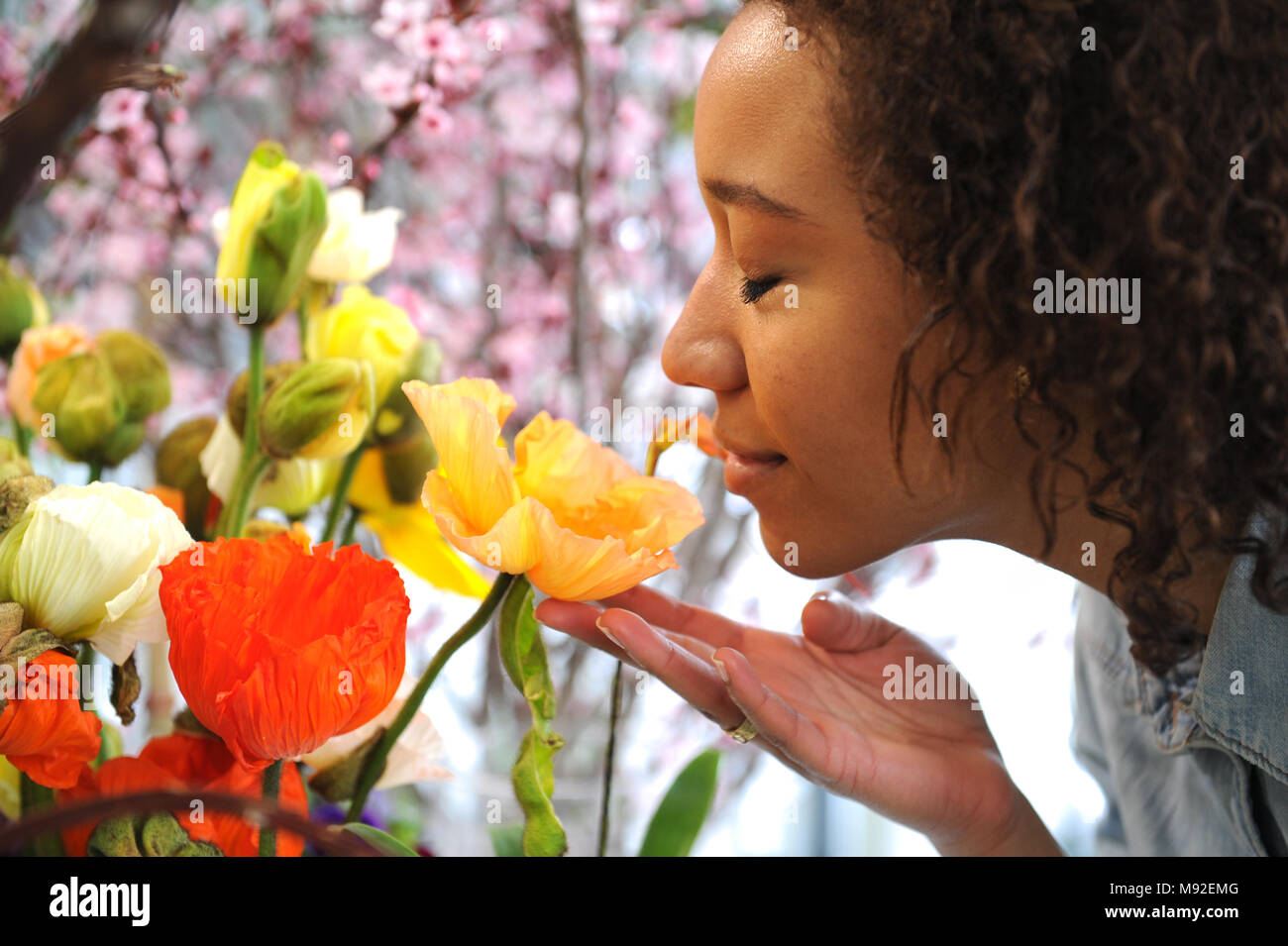 Consumerism: Woman smelling fresh flowers.  - Stock Image