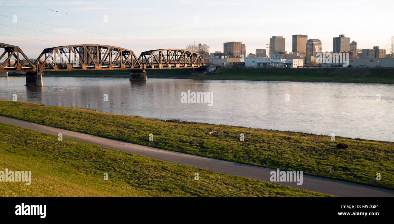 The streets and buildings of Dayton Ohio only have a few travelers early Sunday morning Mad River flowing by - Stock Image