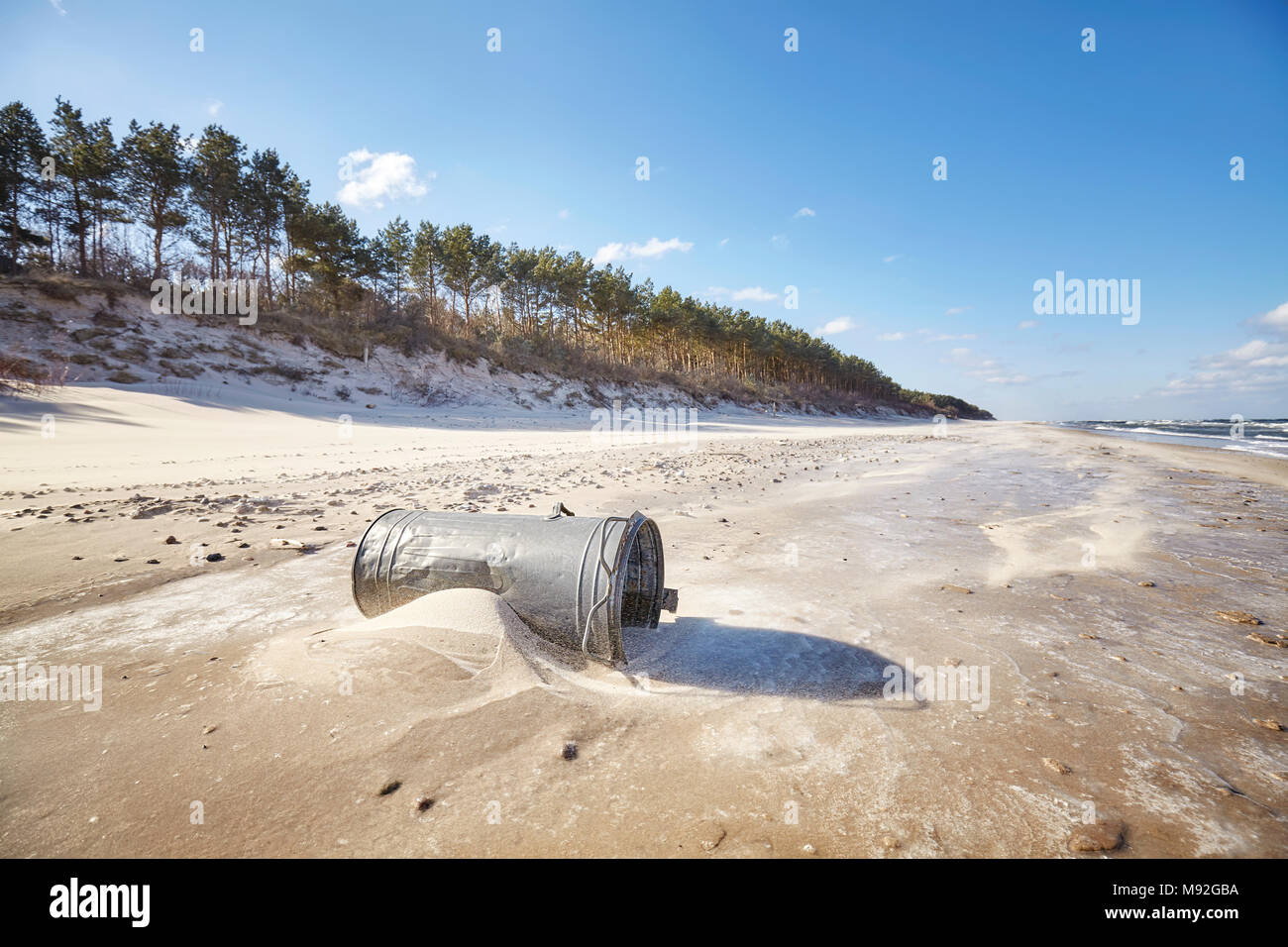 Old trash can on a beach, environmental pollution concept. - Stock Image