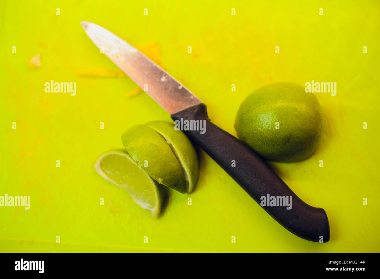lemon lime slices with mint leaves and knife on stone board - Stock Image