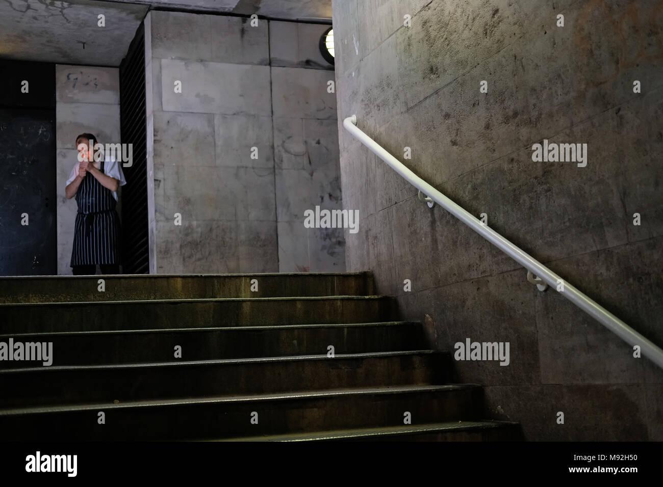 Man smoking in London underpass. - Stock Image