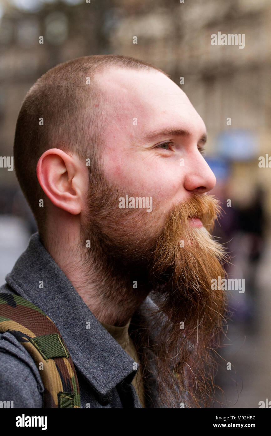 A young man with short hear and long beard stops to have his profile photograph taken in Dundee city centre, UK. Stock Photo