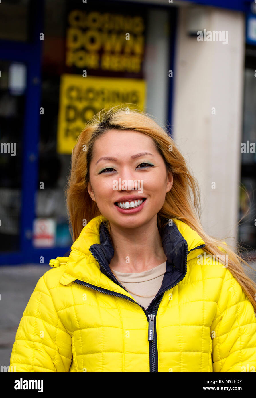 A Scottish born Chinese woman with a happy smiling face posing to have her photograph taken on a windy day in Dundee, UK Stock Photo