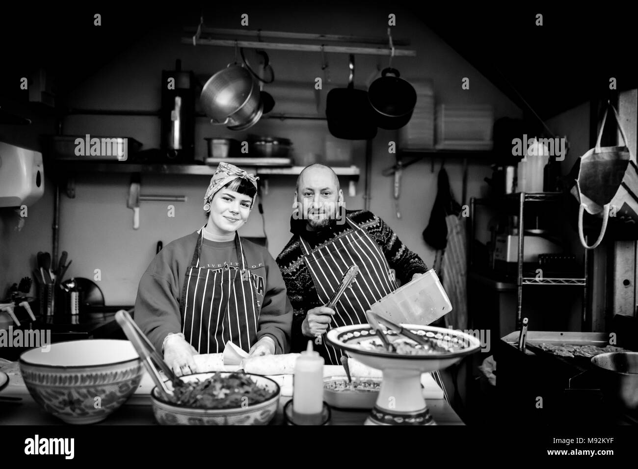 The Shambles, York 16th February 2018. Woman in a head scarf and male man chef in an apron on a hot food stand, stall or kitchen posing for the camera - Stock Image
