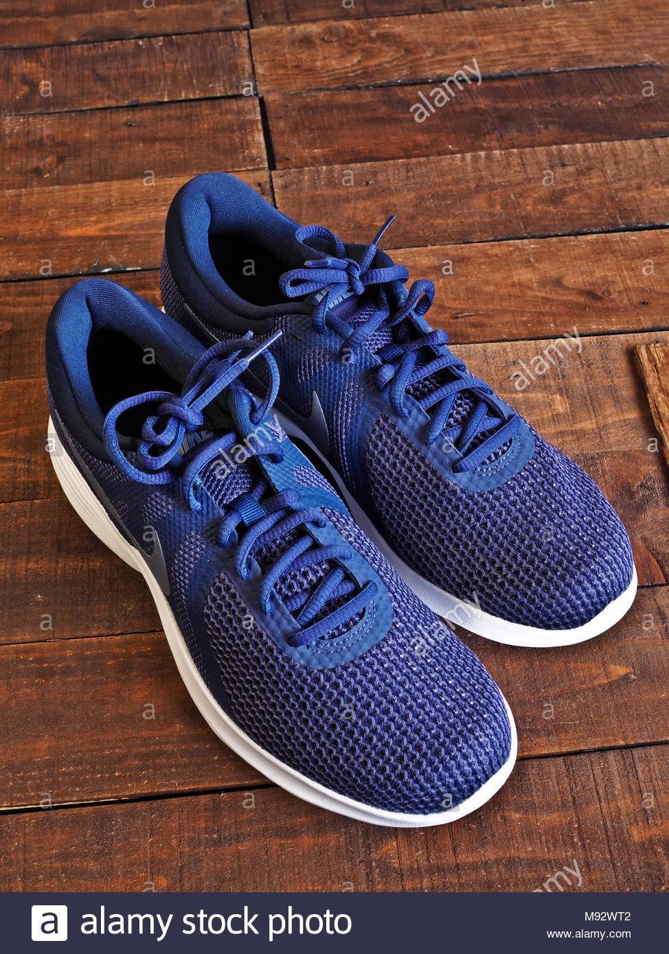 Pair of men's blue lace-up Nike trainers, on dark wooden background with copy space - Stock Image