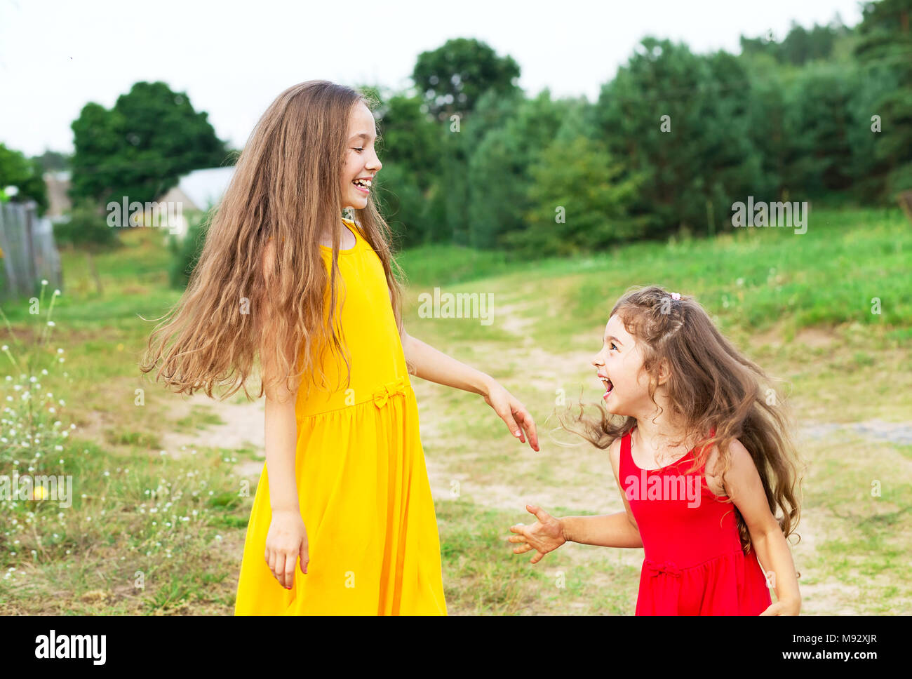 Two beautiful little girls playing and smiling at sunny summer day outdoors. Happy childhood concept - Stock Image