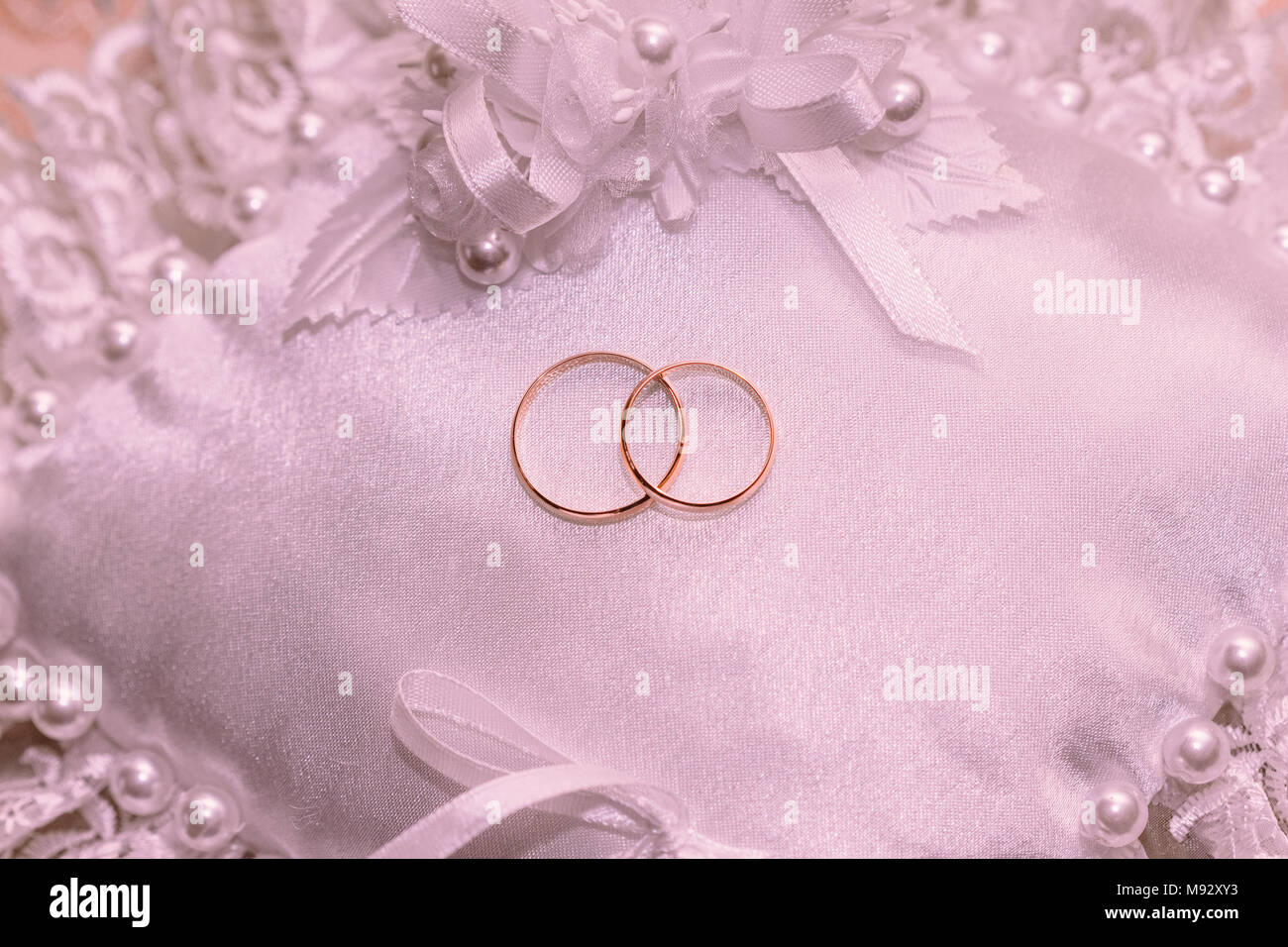 Golden wedding rings on a white pillow top view Stock Photo ...