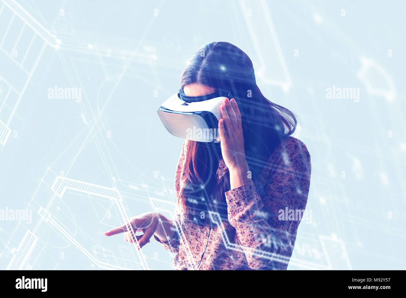 Young woman with virtual reality glasses. The concept of future technology. The concept of a remote study. - Stock Image