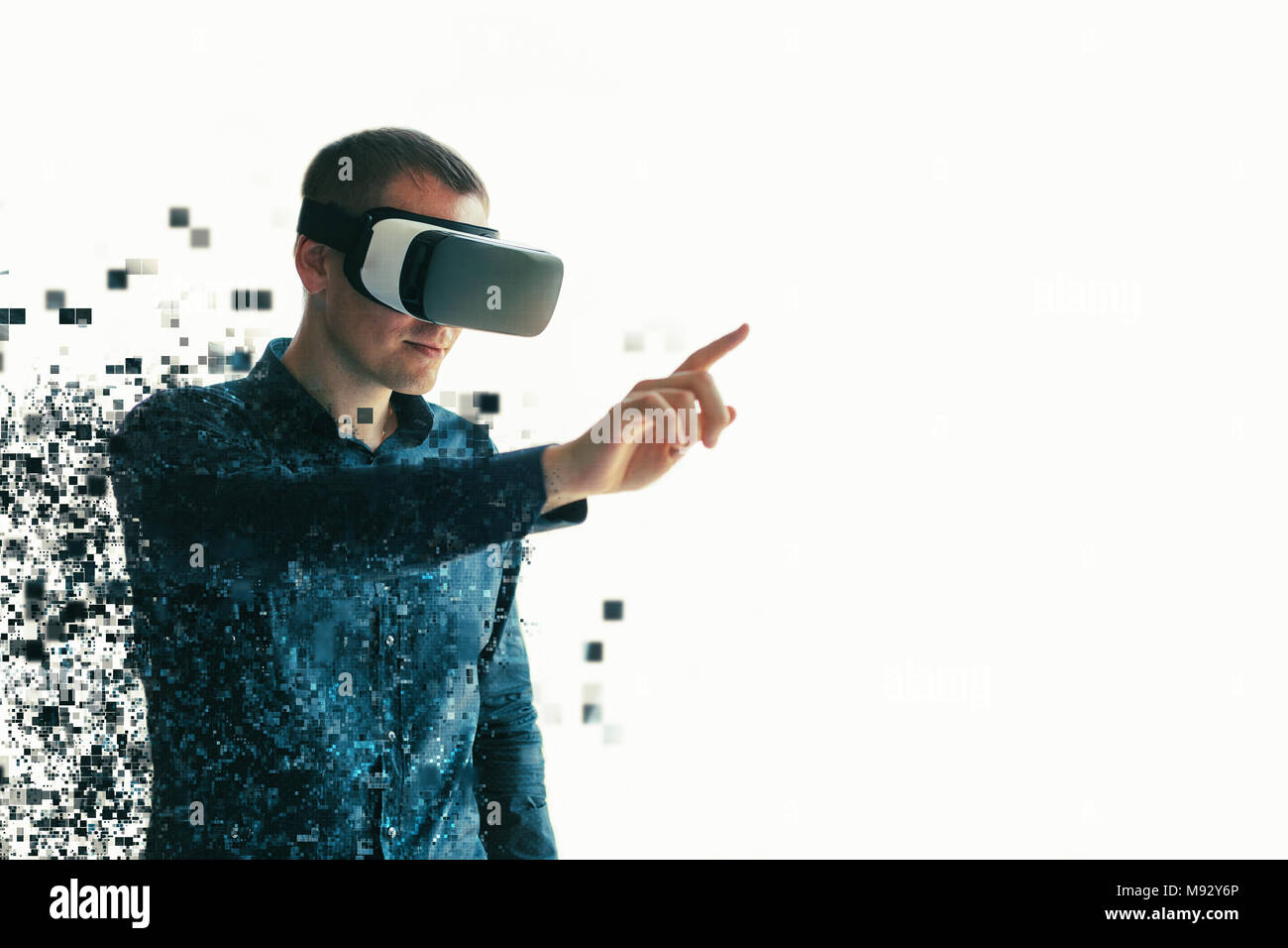 Young man with virtual reality glasses. The concept of future technology. Fragmented by pixels - Stock Image