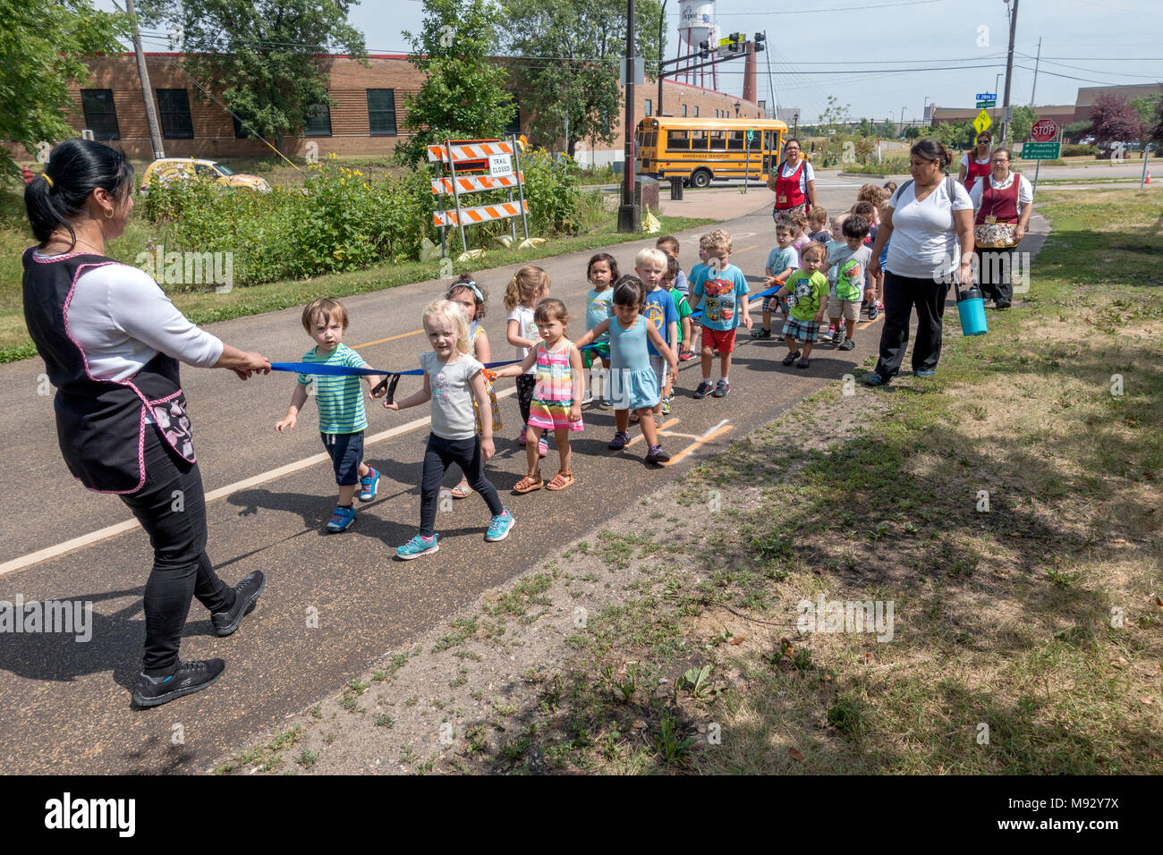 Daycare children age 3 holding a looped strap walking along the Midtown Greenway bicycle & pedestrian trail. Minneapolis Minnesota MN USA Stock Photo