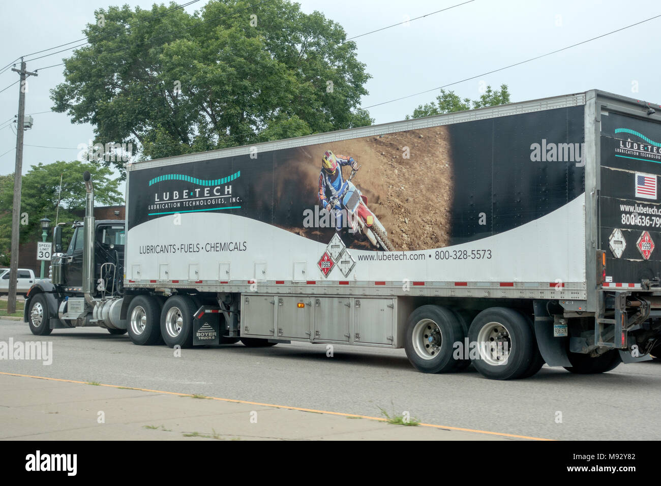 Image of a dirt bike off-road motorcycle in action on the side of a Lube -Teck 18 wheeler semi-trailer truck. Minneapolis Minnesota MN USA - Stock Image
