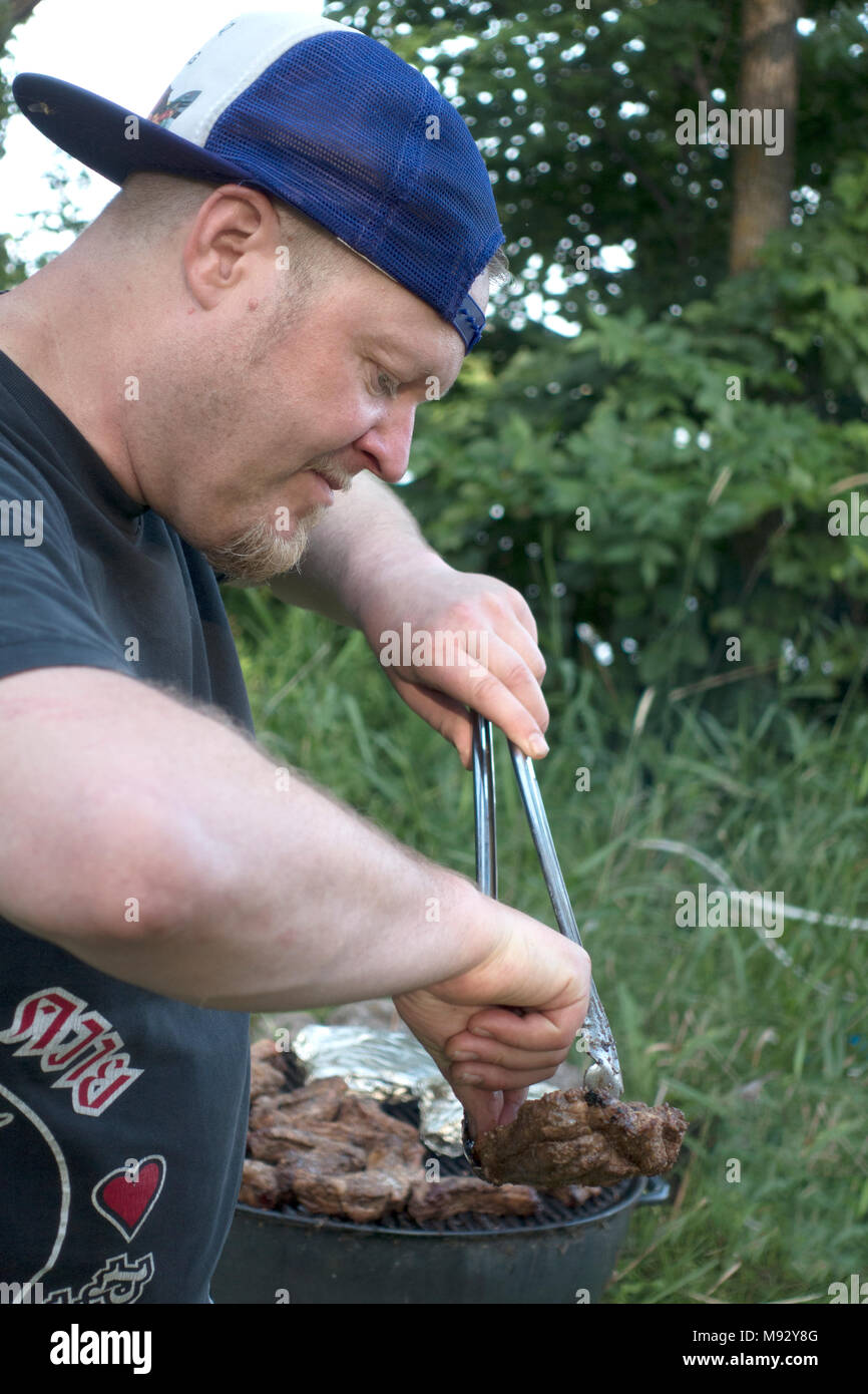 Man age 42 working hard grilling at an outdoor kettle barbecue with tongues in hand. Clitherall Minnesota MN USA - Stock Image