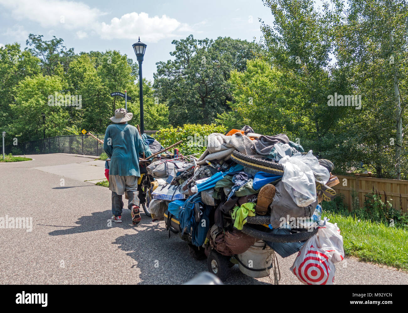 Man on the move with all his belongings stacked on his bicycle and cart traveling on the Midtown Greenway trail. Minneapolis Minnesota MN USA - Stock Image