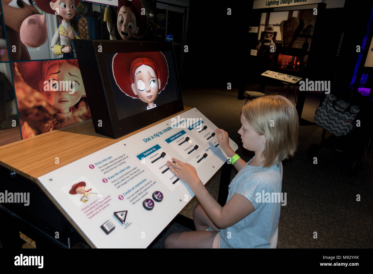 Young girl working at the Pixar Toy Story expression rig controlling upper and lower eyelids and eyebrows Science Museum. St Paul Minnesota MN USA - Stock Image