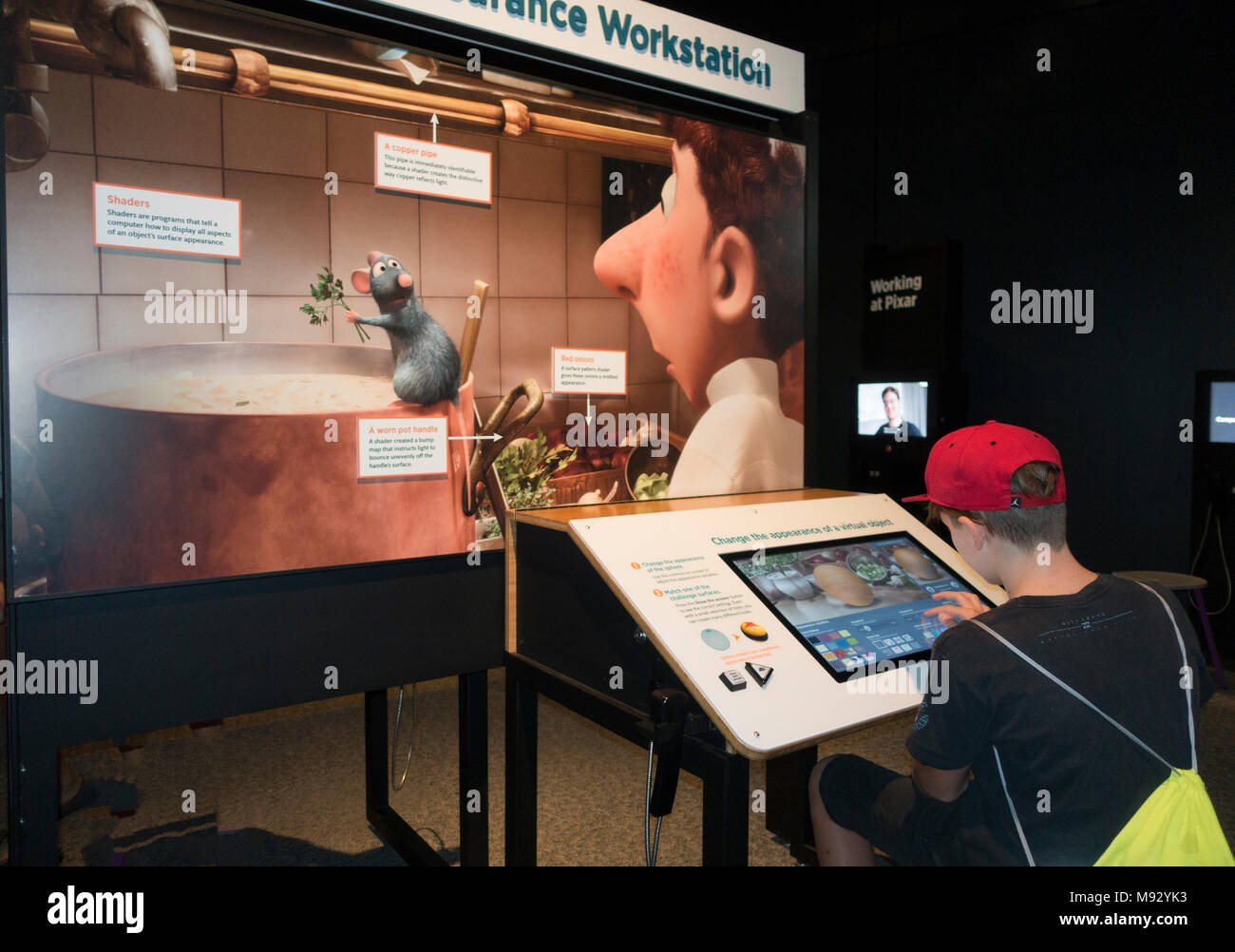 Boy age 12 at workstation changing appearances in Movie Ratatouille  'The Science Behind Pixar' at MN Science Museum.  St Paul Minnesota MN USA - Stock Image
