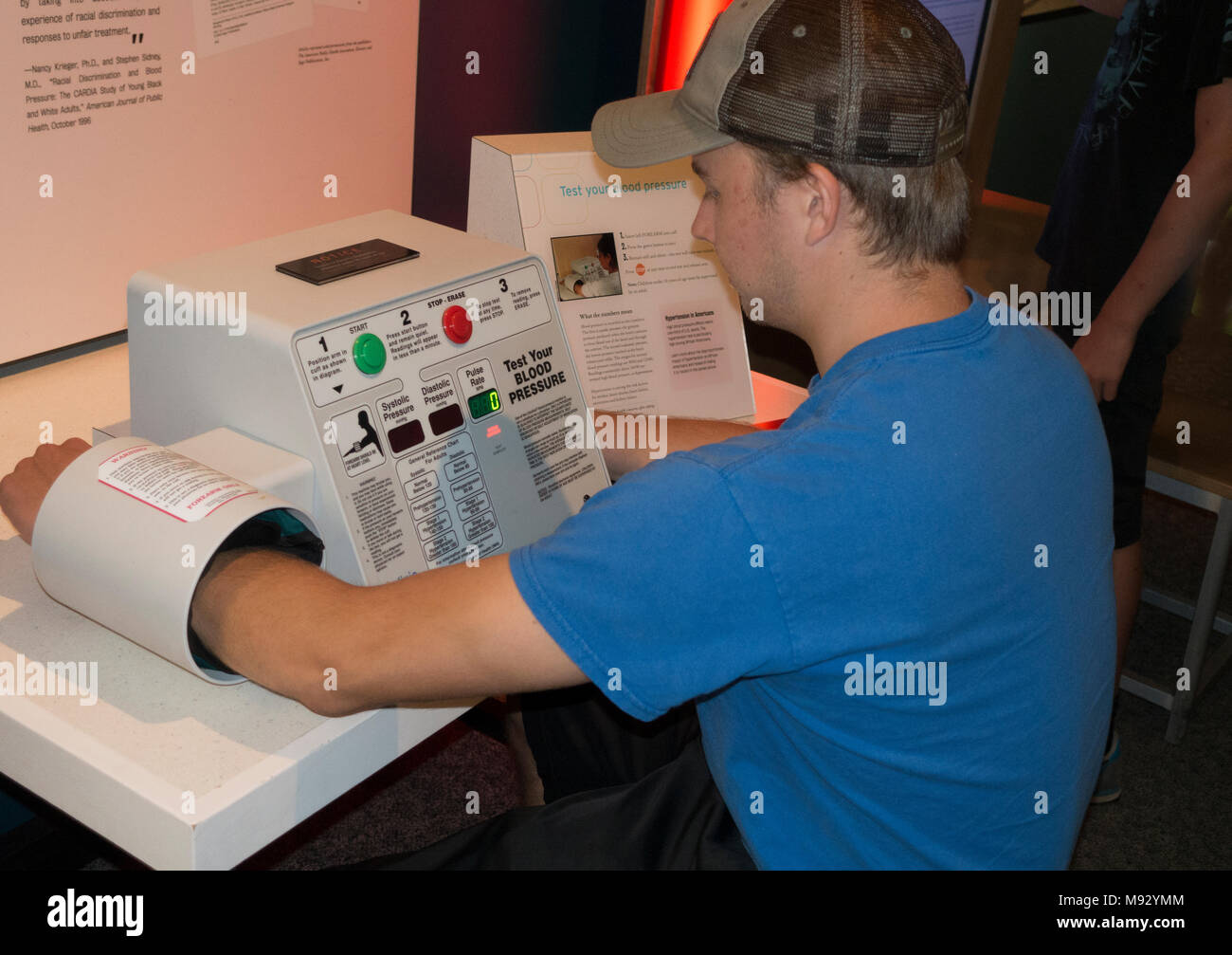 Teenage boy testing blood pressure on an automated machine in an Science Museum exhibit discussing race involved research. St Paul Minnesota MN USA - Stock Image